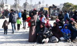 Syryjscy cywile czekający w punkcie kontrolnym obsadzonym przez siły prorządowe, na rondzie ulicy al-Hawoz, po opuszczeniu w sobotę wschodnich dzielnic Aleppo. (AFP)